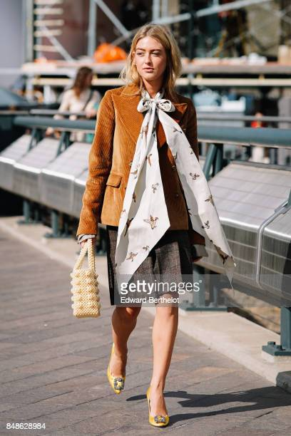Emili Sindlev wears a brown suede blazer jacket a scarf yellow shoes outside Versus during London Fashion Week September 2017 on September 17 2017 in...