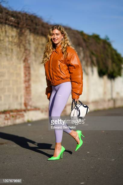 Emili Sindlev wears a brown/orange leather bomber jacket, a white bag, pale purple leggings, green pointy shoes, outside Prada, during Milan Fashion...