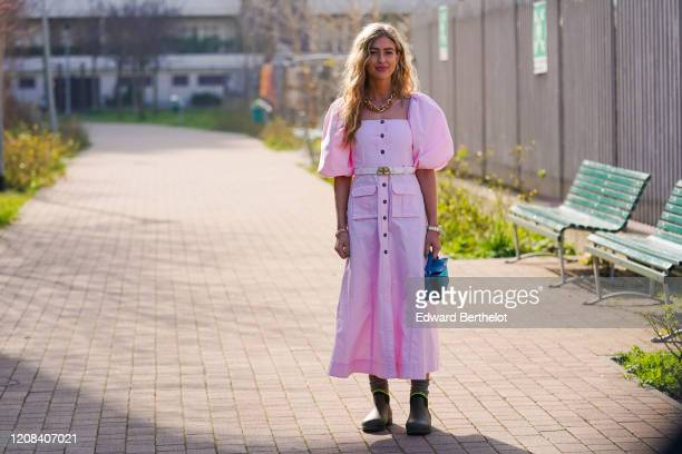 Emili Sindlev wears a golden chain necklace a pink dress with puff shoulder parts a belt a blue bag green khaki boots outside BOSS during Milan...