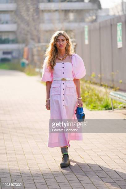 Emili Sindlev wears a golden chain necklace, a pink dress with puff shoulder parts, a belt, a blue bag, green khaki boots, outside BOSS, during Milan...