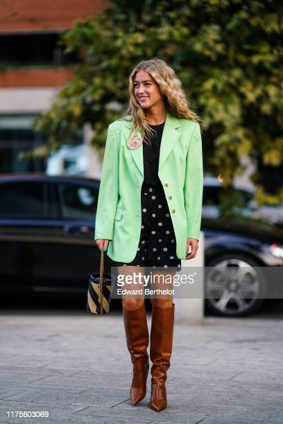 Emili Sindlev wears a green blazer jacket a black top a skirt with floral print brown leather high boots a striped bag outside the Alberta Ferretti...