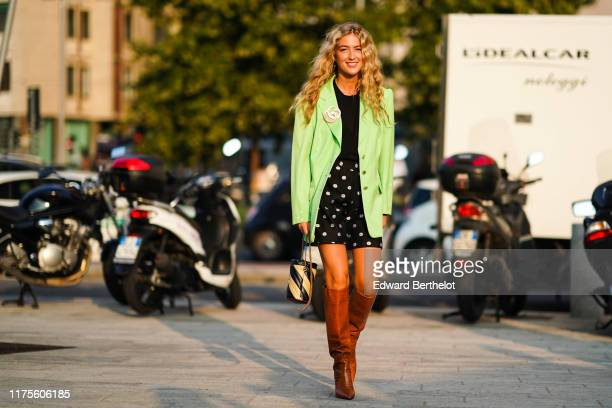 Emili Sindlev wears a green blazer jacket, a black top, a skirt with floral print, brown leather high boots, a striped bag, outside the Alberta...