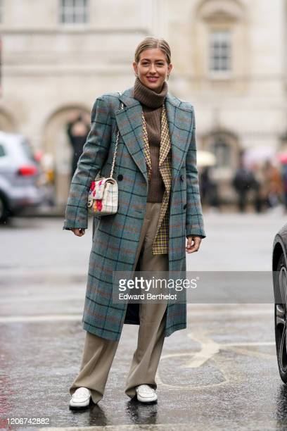 Emili Sindlev wears a green checked long coat a floral print Chanel bag a brown wool turtleneck pullover beige flowing pants white shoes during...