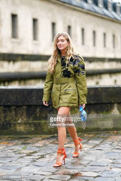 Emili Sindlev wears a green/khaki jacket/dress with floral print, a blue Valentino studded bag, orange high heeled shoes, earrings, outside...