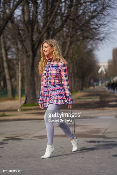 Emili Sindlev wears a pink and blue checked pattern tweed long jacket/dress with ruffled collar, a Chanel quilted silver bag, gray leggings, white...