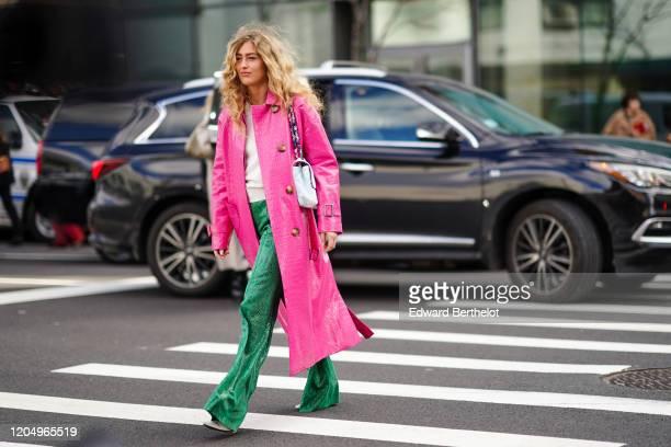 Emili Sindlev wears a pink crocodile pattern coat, a white bag, green snake print flared pants, a white top, outside Self Portrait, during New York...
