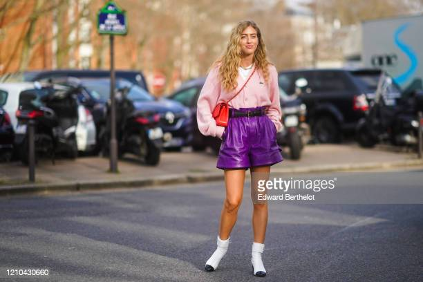 Emili Sindlev wears a pink Lacoste jacket, a white t-shirt, a necklace, a red Chanel crossbody bag, a belt, purple leather shorts, white Chanel...
