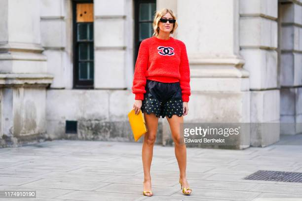 Emili Sindlev wears a red Chanel logo wool pullover black quilted shorts with printed features a yellow rectangular clutch golden shoes sunglasses...