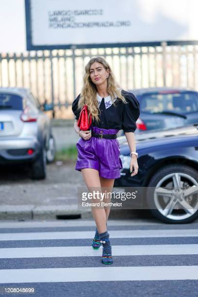 Emili Sindlev wears a ruffled black shirt with puff shoulder pads a red quilted bag purple leather shorts gray wool socks multicolor shoes outside...
