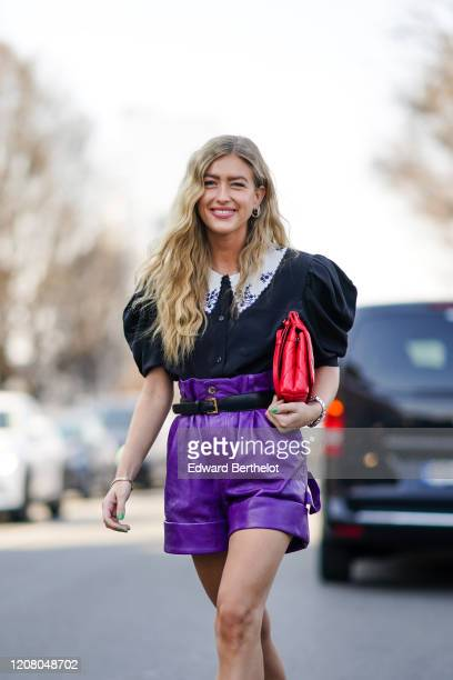 Emili Sindlev wears a ruffled black shirt with puff shoulder pads, a red quilted bag, purple leather shorts, outside MSGM, during Milan Fashion Week...
