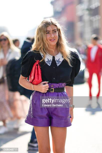Emili Sindlev wears a ruffled black shirt with puff shoulder pads, a red quilted bag, purple leather shorts, a belt, outside MSGM, during Milan...