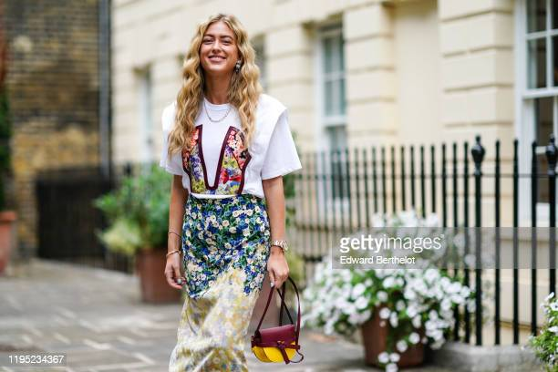 Emili Sindlev wears a t-shirt with colored floral print, a floral print skirt, a burgundy and yellow leather bag from Loewe, during London Fashion...