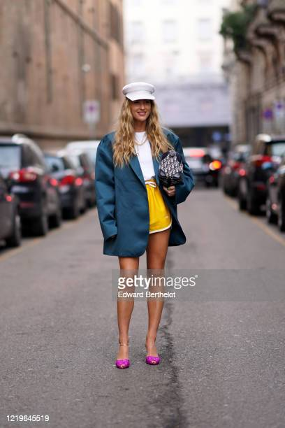 Emili Sindlev wears a white cap hat, a green oversized blazer jacket, a white t-shirt, a Dior monogram bag, yellow shorts, neon pink pointy shoes,...