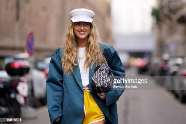 Emili Sindlev wears a white cap hat, a green oversized blazer jacket, a white t-shirt, a Dior monogram bag, yellow shorts, outside Sportmax, during...