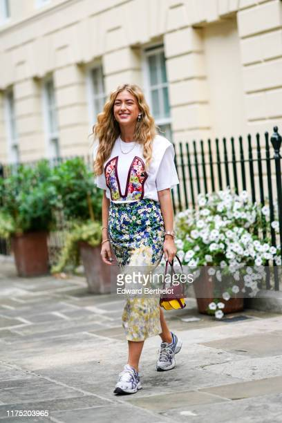 Emili Sindlev wears a white shirt with floral print, a floral print colored skirt, a pearl necklace, a Loewe bag, sneakers during London Fashion Week...