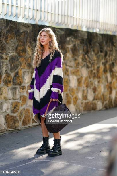 Emili Sindlev wears a wool striped purple black and white dress with oversized sleeves, a large bag, black leather shoes, outside Loewe, during Paris...