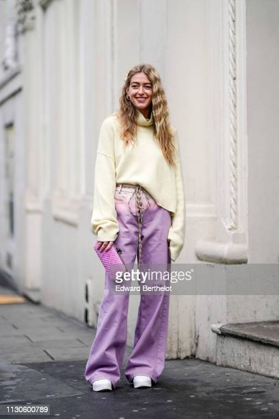 Emili Sindlev wears a yellow turtleneck top with oversized sleeves, pale purple flare pants, a purple clutch, white shoes, during London Fashion Week...