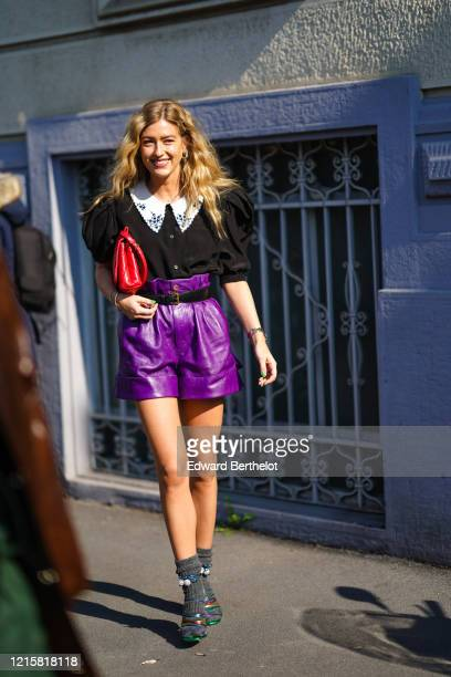 Emili Sindlev wears bracelets, a black top with puff sleeves and a white embroidered collar, a black belt, purple leather shorts, grey socks, heeled...