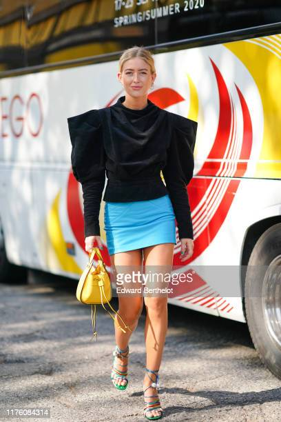 Emili Sindlev wears earrings, a black ruffled puff sleeves top, a blue skirt, a yellow bag, shoes, outside the Marni show during Milan Fashion Week...