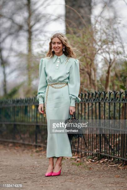 Emili Sindlev wears earrings a light green dress a golden Chanel belt a black studded and decorated with ostrich feathers fringe bag hot pink pointy...