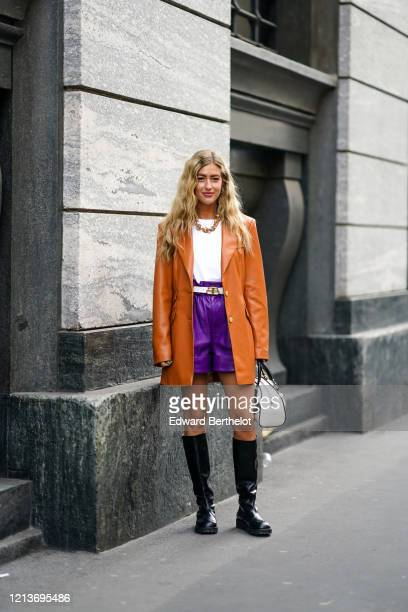 Emili Sindlev wears earrings, a necklace, a white top, a Balenciaga white belt, a tan-color leather long jacket, purple leather shorts, black...