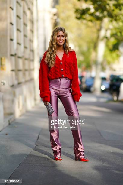 Emili Sindlev wears earrings a red wool Vneck top lustrous pink fulllength pants red heels with a bejeweled buckle a glittering bejeweled clutch...