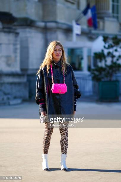 Emili Sindlev wears earrings, a shiny black oversize coat, a neon-green Chanel bag, beige and brown leopard print leggings, white and black Chanel...