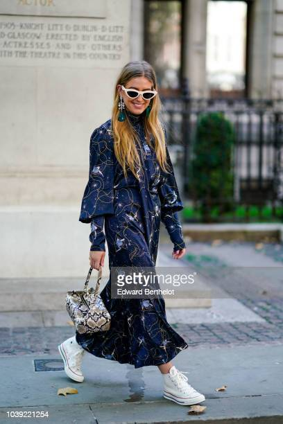 Emili Sindlev wears sunglasses a blue dress with printed features a snake print rectangular bag white sneakers shoes during London Fashion Week...