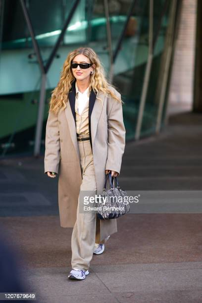 Emili Sindlev wears sunglasses, a gray long jacket with oversized long sleeves, a white top, a cream color shirt, a Dior monogram bag, flared pants,...