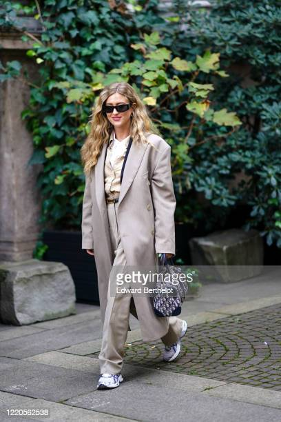 Emili Sindlev wears sunglasses, a gray long oversized coat, a Dior bag, a shirt, flare pants, sneakers, outside Koche x Pucci, during Milan Fashion...