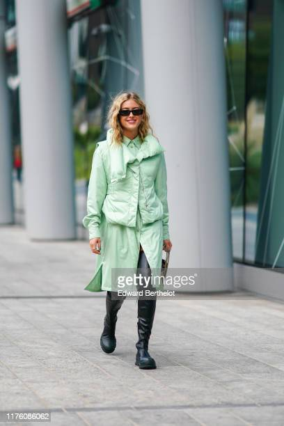 Emili Sindlev wears sunglasses a green puffer jacket a green shirt dress a yellow and black striped bag black leather boots outside the Sportmax show...