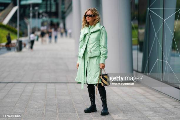 Emili Sindlev wears sunglasses, a green puffer jacket, a green shirt dress, a yellow and black striped bag, black leather boots, outside the Sportmax...