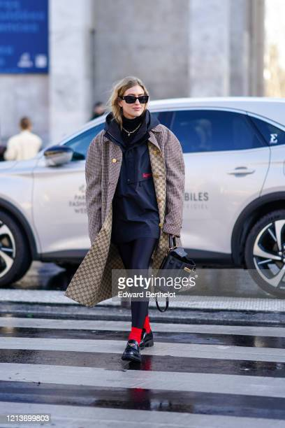 Emili Sindlev wears sunglasses, a Supreme jacket with a hood, a Gucci long oversized coat with houndstooth patterns and printed logos on the inner...