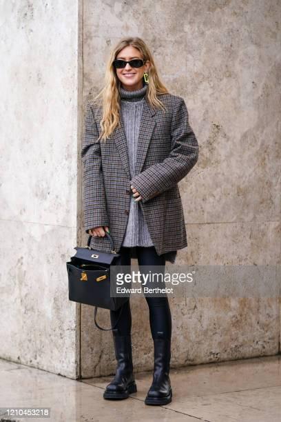 Emili Sindlev wears sunglasses, earrings, a grey turtleneck, a grey houndstooth oversized jacket, black leggings, black mid-calf boots, a black bag,...