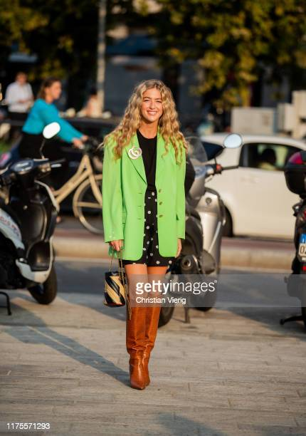 Emili Sinlev is seen wearing shorts with dots print green blazer striped bag brown boots outside the Alberta Ferretti show during Milan Fashion Week...