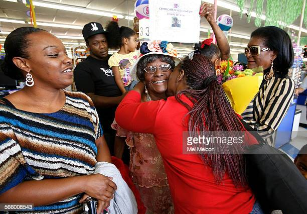 Emilia DeFour center receives a kiss from friend Orlett Smith after completing a free shopping spree inside the 99 Cents Only store in Paramount on...