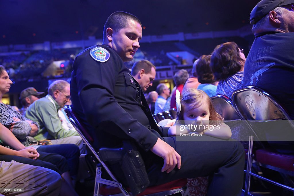 Emilia Pesquera rests on the lap of her father Marcus as he listens to speakers at the National Rifle Association's NRA-ILA Leadership Forum during the NRA Convention at the Kentucky Exposition Center on May 20, 2016 in Louisville, Kentucky. Marcus Pesquera was chosen by the NRA as the officer of the year. The convention, which opened today, runs until May 22.