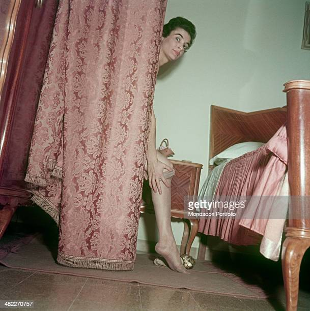 Emilian girl Lidia Rodolfi wearing a pair of sheer nude tights behind the curtain in a bedroom Italy 1955
