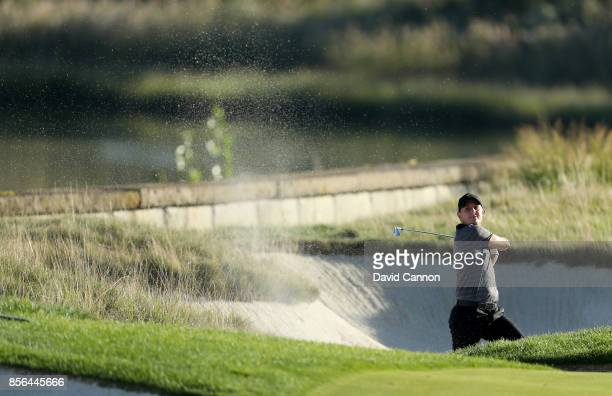 Emiliano Grillo of Argentina and the International team plays his second shot at the 14th hole in his match against Rickie Fowler during the final...