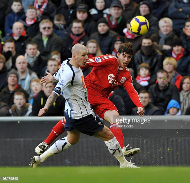 Emiliano Insua of Liverpool competes with Gretar Rafn Steinsson of Bolton Wanderers during the Barclays Premier League match between Liverpool and...