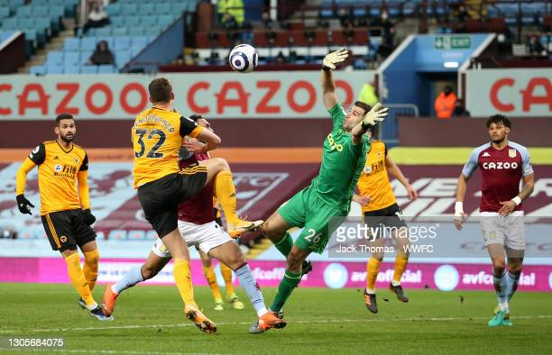Emiliano Martinez of Aston Villa attempts to collect the ball as Ahmed El Mohamady of Aston Villa and Leander Dendoncker of Wolverhampton Wanderers...