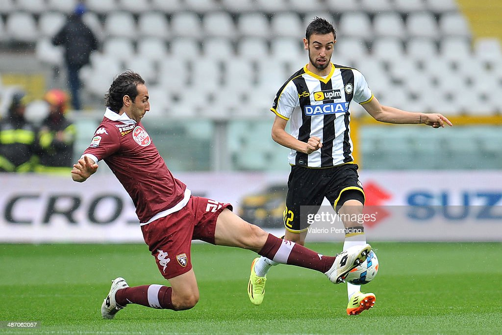 Emiliano Moretti (L) of Torino FC tackles Bruno Fernandes of Udinese Calcio during the Serie A match between Torino FC and Udinese Calcio at Stadio Olimpico di Torino on April 27, 2014 in Turin, Italy.