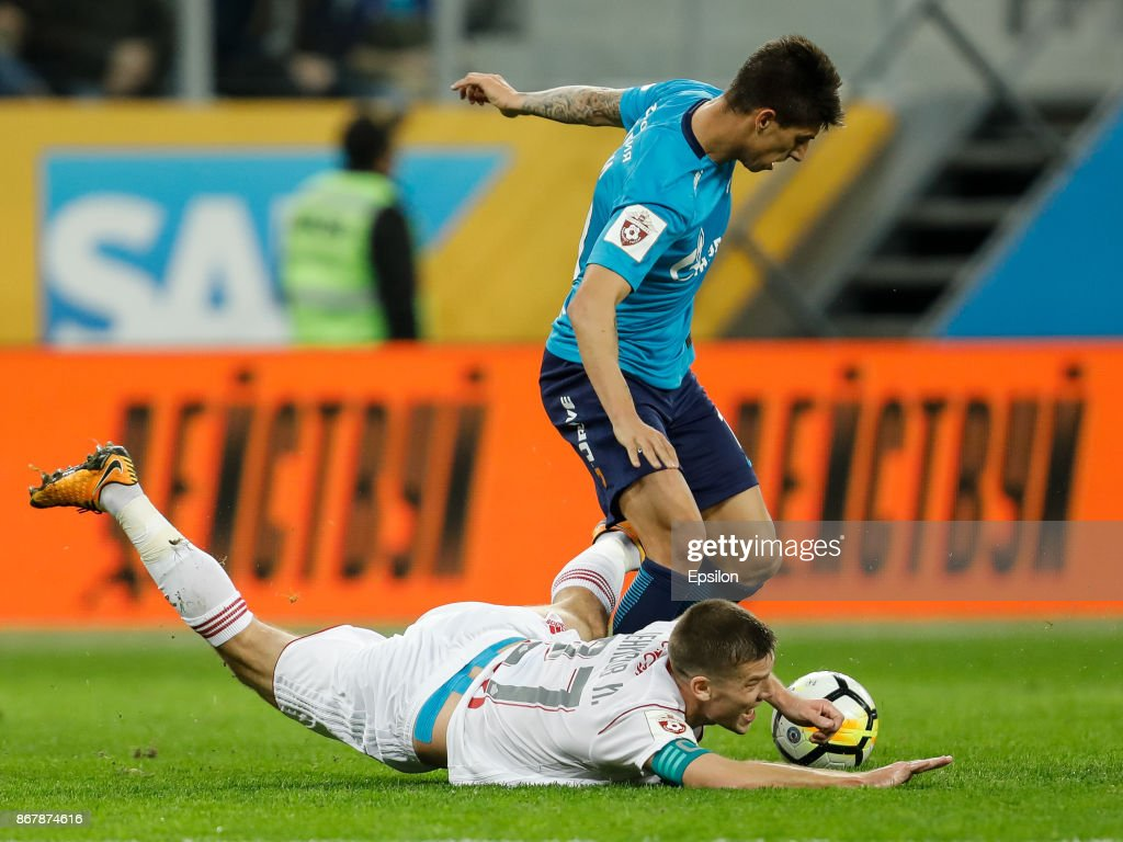 Emiliano Rigoni (top) of FC Zenit Saint Petersburg and Igor Denisov of FC Lokomotiv Moscow vie for the ball during the Russian Football League match between FC Zenit St. Petersburg and FC Lokomotiv Moscow on October 29, 2017 at Saint Petersburg Stadium in Saint Petersburg, Russia.