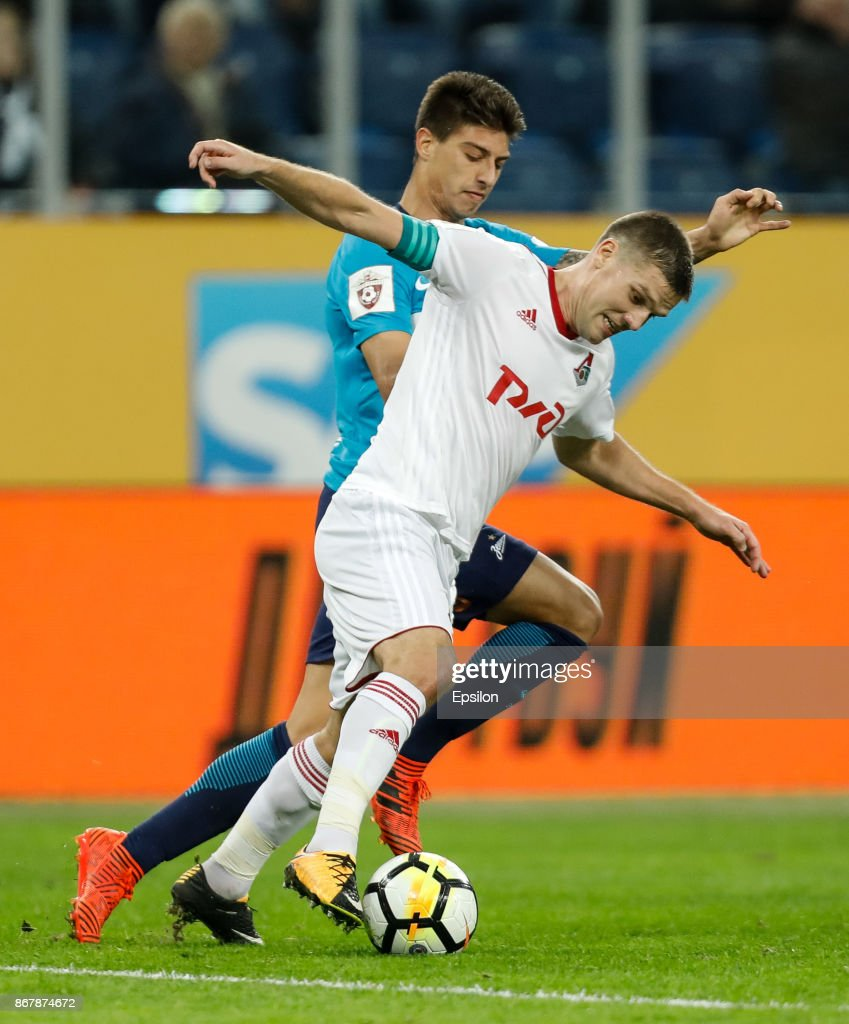 Emiliano Rigoni of FC Zenit Saint Petersburg and Igor Denisov (in front) of FC Lokomotiv Moscow vie for the ball during the Russian Football League match between FC Zenit St. Petersburg and FC Lokomotiv Moscow on October 29, 2017 at Saint Petersburg Stadium in Saint Petersburg, Russia.