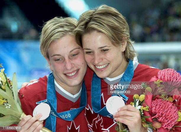Emilie Heymans and Anne Montminy of Canada display their silver medals after the women's synchronized 10m platform final of the diving competition 28...