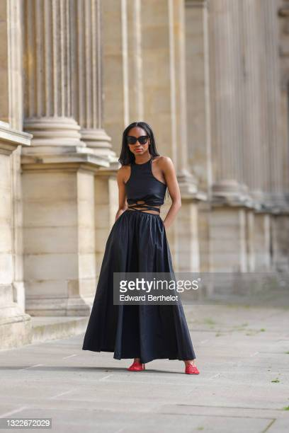 Emilie Joseph @in_fashionwetrust wears a black solid strap detail tank-top and matching midi skirt from mango, red mesh sandals by Bottega Veneta...