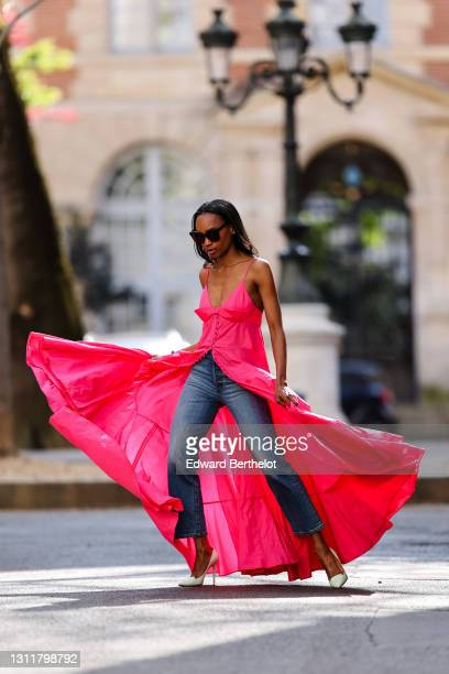 Emilie Joseph @in_fashionwetrust wears a Jacquemus Manosque Maxi flowing pleated low-neck dress in bright neon pink taffeta, worn with high-waisted...