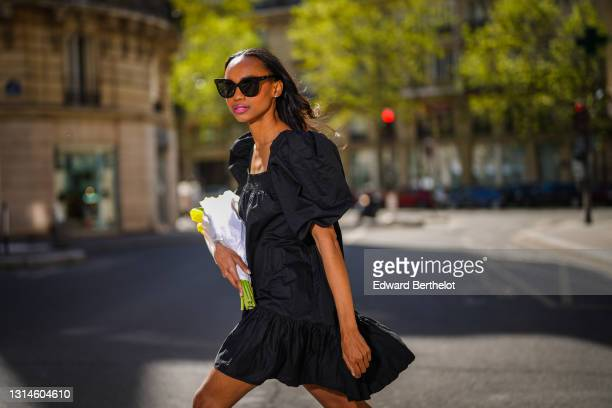 Emilie Joseph @in_fashionwetrust wears a short A-line dress in woven cotton with tiered skirt with gathered ruffles, square neckline, short puffed...