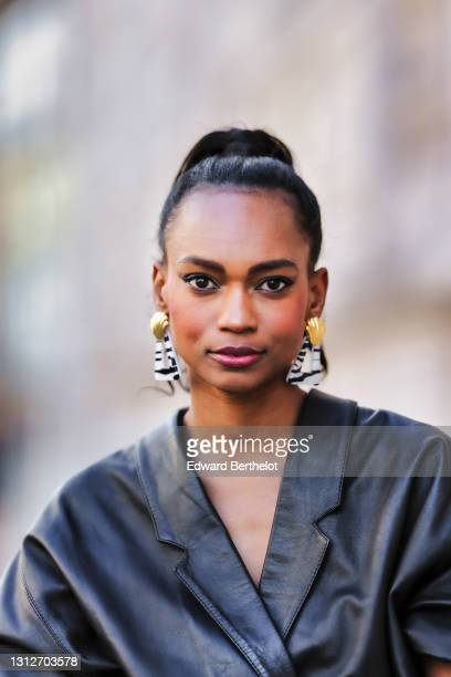 Emilie Joseph @in_fashionwetrust wears a vintage soft leather oversized shirt, zebra earrings with golden parts from Rixo London, on April 15, 2021...