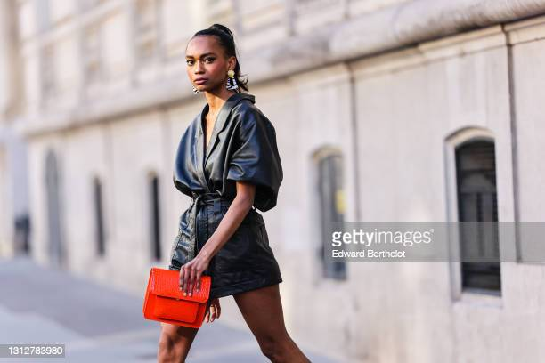 Emilie Joseph @in_fashionwetrust wears a vintage soft leather oversized shirt tucked into leather shorts, zebra earrings from Rixo London, a...